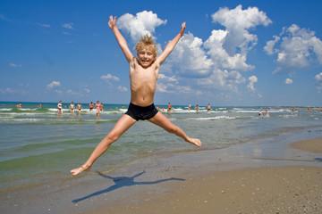 Flying boy on a beach