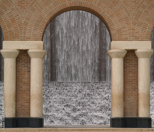 view of a waterfall through an archway made of stone - 3943502
