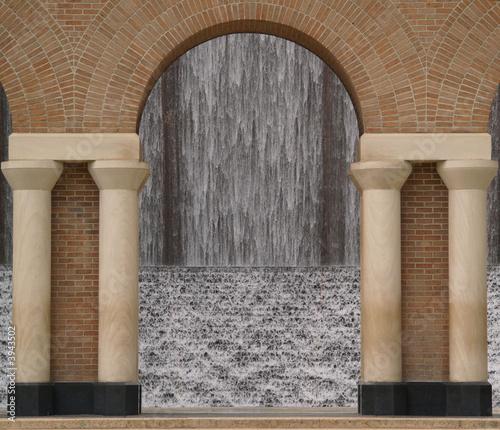 Leinwandbild Motiv view of a waterfall through an archway made of stone