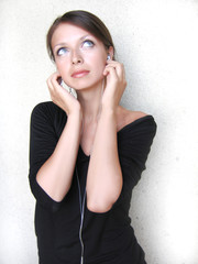 Beautiful girl listening to the music with small headphones
