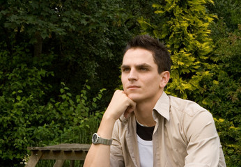 Young Man Outside at Picnic Table with chin on hand