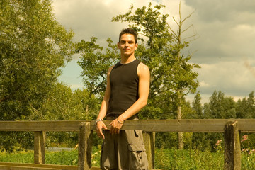 Young Man Standing on Wooden Bridge