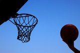 Player jumping toward a basketball hoop against blue sky poster