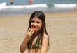 petite fille qui mange sur la plage