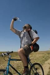 Radfahrer trinkt vor blauem Himmel
