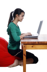 Young pretty women on red bean bag relaxing and using laptop
