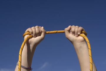 Two hands with an orange rope on sky background