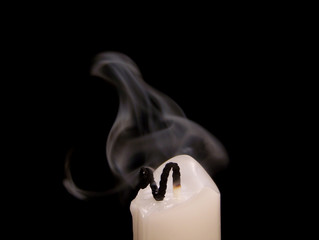 Extinguished candle with smoke floating above it