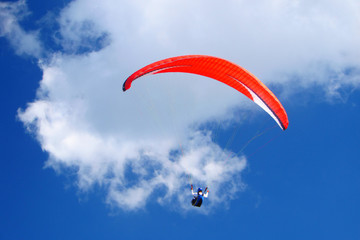 Red paraglider on blue sky