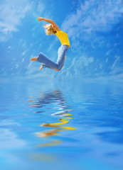 Beautiful blonde girl jumps over water