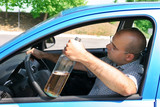 Drunk man sitting in drivers and holding a bottle alcohol poster