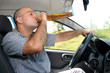 Drunk man sitting in drivers sit and drinking from a bottle