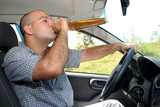 Drunk man sitting in drivers sit and drinking from a bottle poster