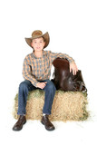 Boy on hay bale with saddle poster