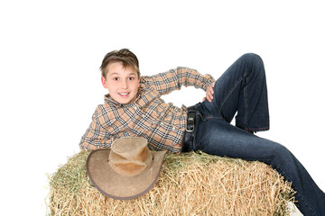 Rural child lying on hay bale