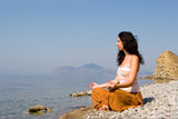 young woman meditation in the beach poster