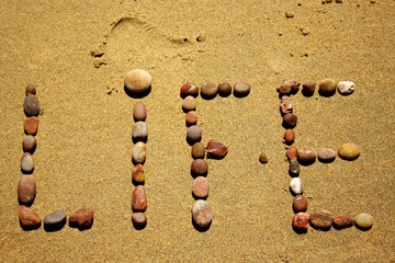 stones in the sand saying life