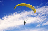Paraglider against a  vibrant blue sky poster