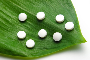 white pills on leaf