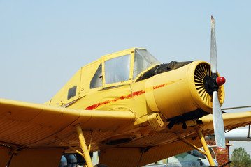 Yellow turboprop airplane on display at museum