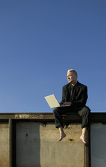Barefoot Punk Businessman on a Wall with Laptop Computer