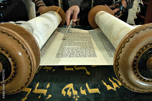 Torah  in a synagogue with a hand holding a silver pointer - 4053703