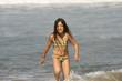 petite fille en maillot de bain qui court sur la plage
