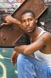 black man behind grungy metal