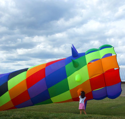 Girl Examines Colorful Wind Sock Kite
