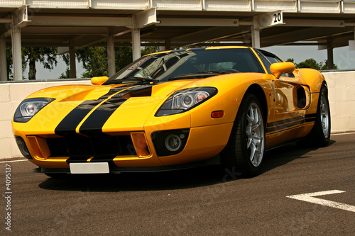 Foto op Canvas Snelle auto s front of yellow supercar with black stripes