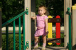 Babygirl in sunset lights on playground