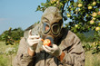 Постер, плакат: Man with gas mask squirting contaminated apple