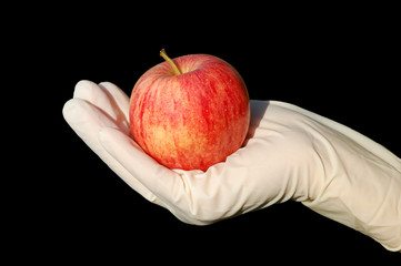 Hand with glove holding apple