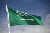 Saudi Arabian flag flying against a blue sky poster
