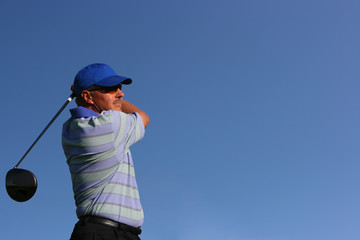 Close up of golfer teeing off on isolated blue