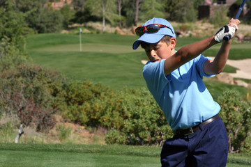 Young male about to tee off with flag visible, focus on golfer