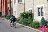 Student cyclist on university campus with flowers poster