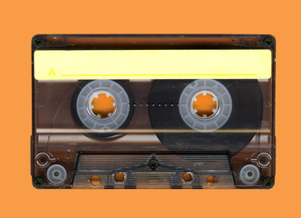 Old Grungy cassette tape isolated over a orange background