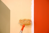 three colors painting a wall with a roll