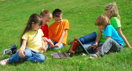 Children outdoors with laptops
