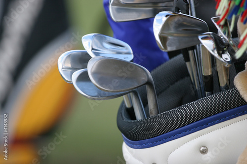 golf bag and set of clubs on green