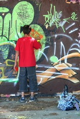 Adolescent en train de peindre un graffiti sur un mur