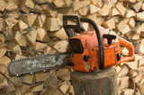 Chainsaw against firewood pile poster