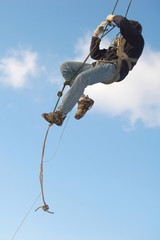 Young man hanging on the rope in the blue sky