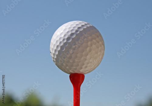 Balle de golf sur tee rouge