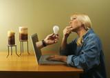 Internet concept. Hand Light Bulb Coming Through Laptop Screen. poster