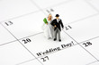 Miniature bride and groom on a calendar that says Wedding Day - 4198152