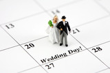 Miniature bride and groom on a calendar that says Wedding Day