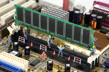 Miniature construction workers installing RAM on a motherboard
