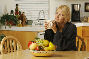 Beautiful, young woman enjoying a cup of coffee in her home.